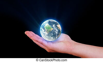Earth In Hand - Man holding a glowing and shining earth in...