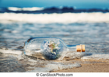 Earth in the bottle coming with wave from ocean. Environment, clean world message