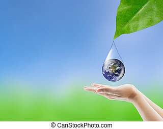 Earth in water drop reflection under green leaf hold hand, Elements of this image furnished by NASA