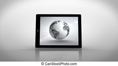 Earth made of cogs and wheels displayed on tablet screen on...