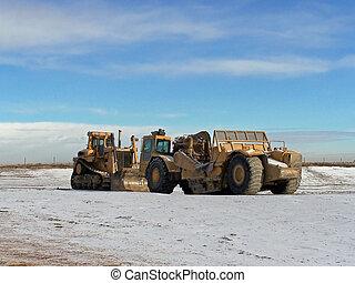 earth movers - bull dozer and a scraper on a job site
