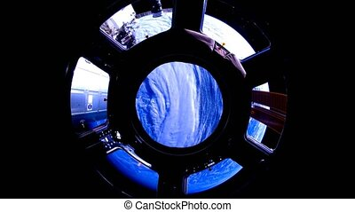 Earth through the porthole of the ISS. Elements of this...