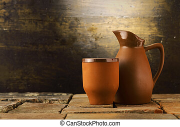 Earthenware mug and pitcher standing on grunge flagstones or tiles in a rustic cellar with copyspace