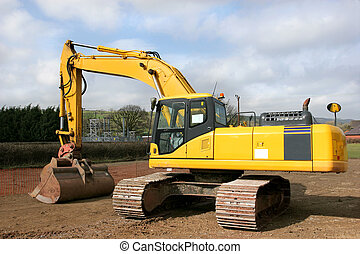 Yellow digger standing idle on a building construction site with an electricity sub station to the rear.