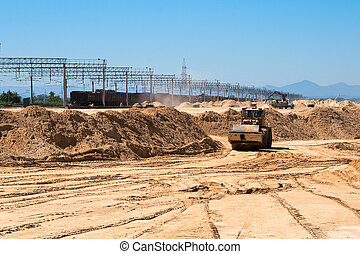 Earthworks, mountains of sand, soil compaction roller