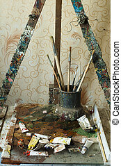 Easel for painting, tubes of oil paint and brushes