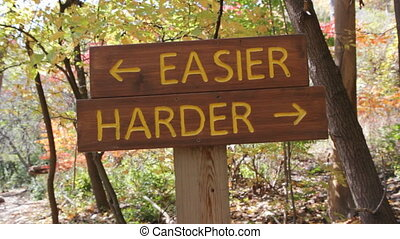 Sign in the woods shows two options. The easier or the harder trail. Don Valley, Toronto, Ontario, Canada.