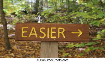 EASIER trail. Biker in background. - Sign shows the...