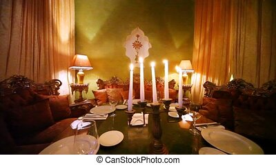 East sofas stands near table on which light candles