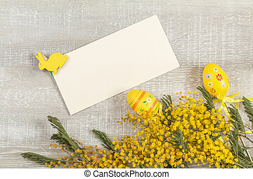 Easter accessories, mimosa and yellow daffodils on a light wooden surface.