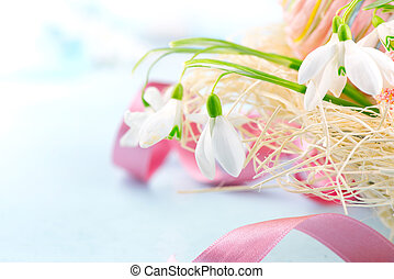 Easter background. Beautiful spring snowdrop flower with decorations on the wooden table