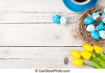 Easter background with blue and white eggs in nest, yellow tulips and coffee cup