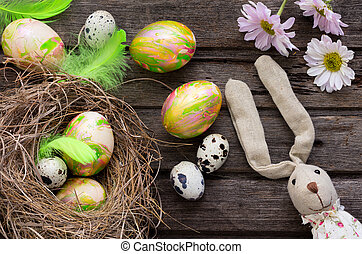 Easter background with colored eggs in nest and home made decoration on rustic wooden board