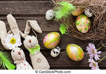 Easter background with colorful eggs in nest and home made bannies on rustic wooden board