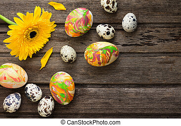 Easter background with eggs and yellow flower on wooden board, top view