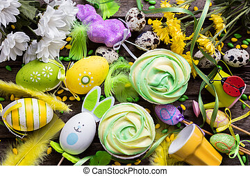 Easter background with eggs, cupcakes, flowers and decoration, top view