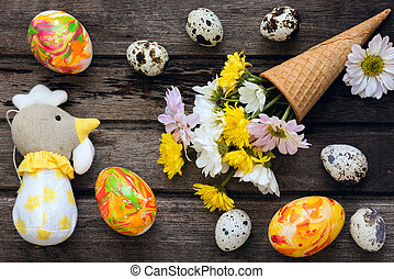 Easter background with eggs, flowers, and home made decoration on wooden board, top view