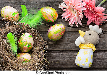 Easter background with eggs in nest and home made decoration on rustic wooden board