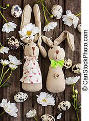 Easter background with home made bannies, eggs, flowers, and decoration on wooden board, top view