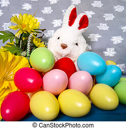 Easter background with plush rabbit, eggs and flower.