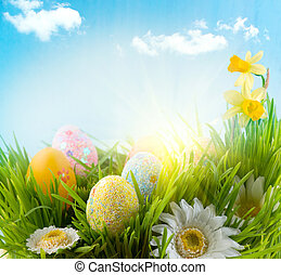 Easter. Beautiful colorful eggs in spring grass meadow over blue sky