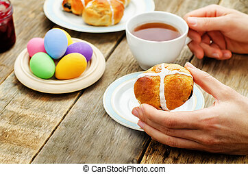 Easter Breakfast. Man holding the bun with a cross and a cup of