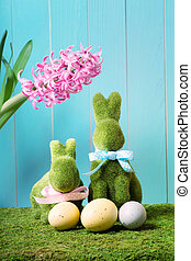 Easter bunnies with eggs and a pink hyacinth flower