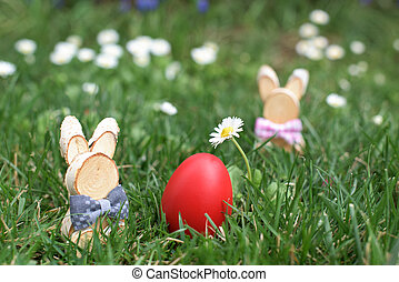 Easter Bunny and red hen Easter egg in a grass