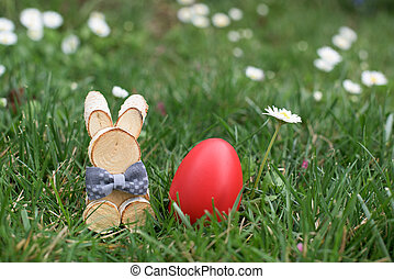 Easter Bunny and red hen Easter egg in a grass and deisies