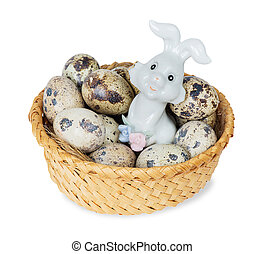 Easter bunny in a basket with quail eggs isolated on white...