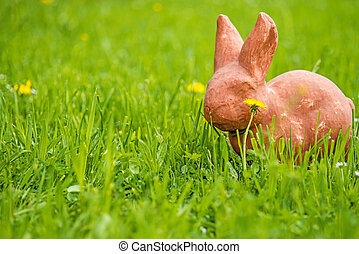 Easter bunny in a green meadow with dandelion flower