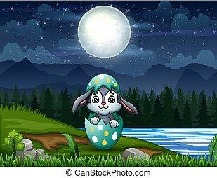 Easter bunny inside a cracked egg in Easter eve