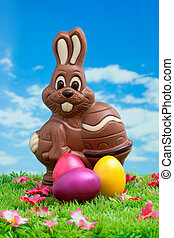 Easter bunny made of chocolate with colorful easter eggs on a green meadow with flowers in front of a blue sky