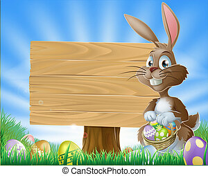 A cute Easter bunny rabbit character standing by a wooden sign holding a basket of decorated Easter eggs surrounded by Easter eggs in a field