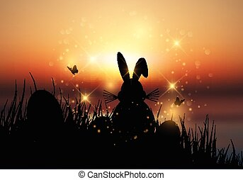 Easter bunny sat in grass against a sunset sky