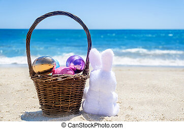 Easter bunny with basket and color eggs on the ocean beach