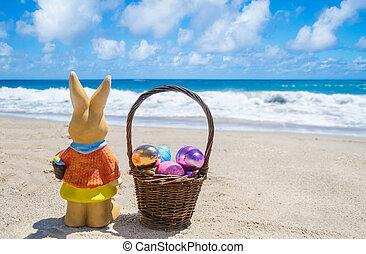 Easter bunny with basketand color eggs on the beach near ocean