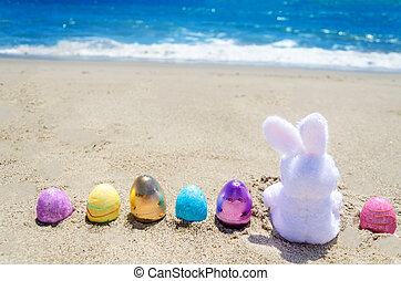 Easter bunny with color eggs on the ocean beach