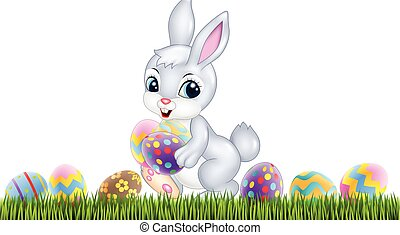 Easter bunny with decorated Easter eggs in a field