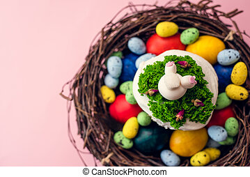 Easter cake decorated with cream in the form of grass and a rabbit butt figurine in a basket on a pink background next to painted quail pastel and chicken eggs. Easter gift card