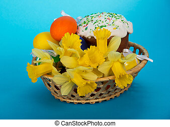 Easter cake, eggs and flowers in a basket, on a blue...