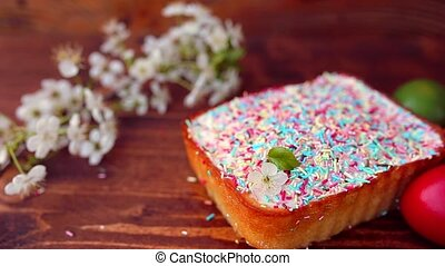 Easter cake on a plate, on a wooden board. The painted eggs in d