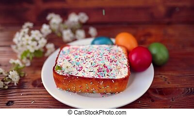 Easter cake on a plate, on a wooden board. The painted eggs