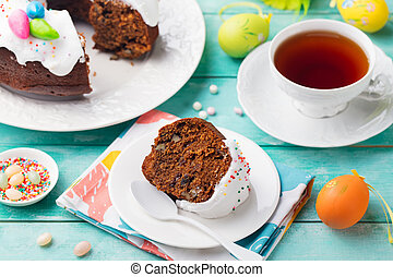 Easter cake on a white plate with colorful eggs. Blue wooden background.