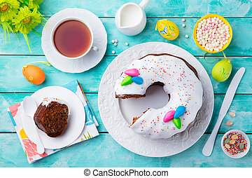 Easter cake with colorful eggs. Blue wooden background. Top view.