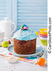 Easter cake with colorful eggs. White and blue wooden background. Copy space.