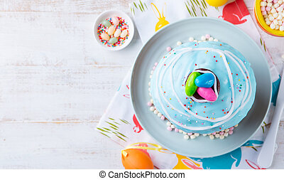 Easter cake with colorful eggs. White wooden background. Top view. Copy space.