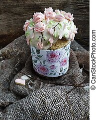 Easter cake with cream roses on wooden background