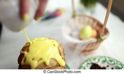 Easter cake with yellow frosting and colorful sprinkles on a white table. Girl watering icing Easter cake