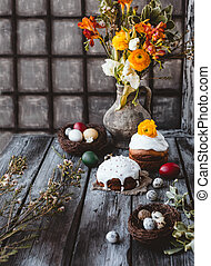 Easter cakes and eggs with spring flowers in jug on table